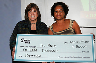 CIREBA President Jeanette Totten (left) presents a donation check to Lynda Mitchell, Manager of the Pines at CIREBA's recent holiday party.