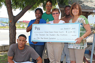 CIREBA President Jeanette Totten (far right) presents a check to representatives from the Cayman Islands Humane Society.