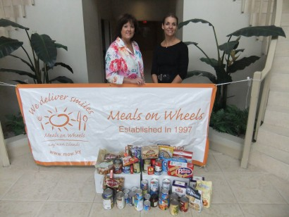Jeanette Totten and Kerri Kanuga stand with some of the donated items to Meals on Wheels.